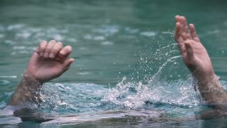 Slow motion close up of a man drowning in water - in a swimming pool, lake, or ocean with a high shutter speed