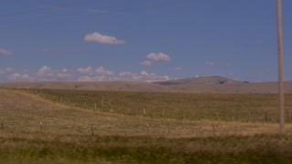 Slow motion driving shot of the wheat fields of rural Montana without people or buildings