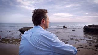 Slow motion handheld arch shot of a middle aged man in casual dress sitting on the beach overlooking the ocean.
