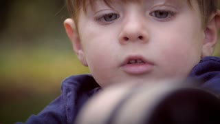 Slow motion of a cute little boy intensely focusing on his toys while playing outside on a beautiful summer day with soft focus.