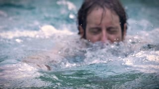 Slow motion of a middle aged man swimming in a pool, river, lake, or ocean. He looks like he is doing the breast stroke
