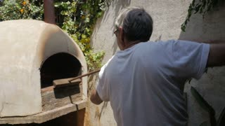 Slow motion of an active senior cleaning a hot wood fired oven with a broom outdoors
