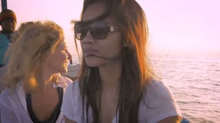 Slow motion of beautiful Asian women and other tourists on a sightseeing boat tour in Bali in the morning sun.
