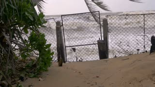 Slow motion of rising sea levels crashing through a closed gate during a storm surge due to climate change