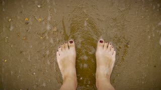 Slow motion of waves gently covering a woman's feet with painted toe nails standing in the sand at the beach