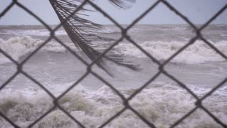 Slow motion rack focus on a chain link fence and a heavy surf from a storm on the ocean representing rising sea levels, climate change, and loss of beach front property