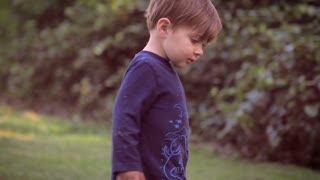 Slow motion shot of a cute and beautiful 2 year old toddler caucasian boy in nature exploring his surroundings while looking around smiling and bending over to pick up something from the grass with his hands.