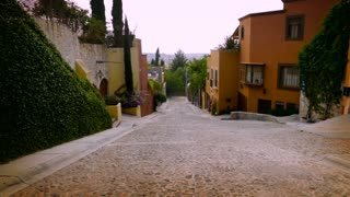 Slow motion steadicam of a cobble stone street with colorful houses and no cars in San Miguel de Allende