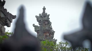 Slow motion tilt and pan of a Balinese Temple seen through a front gate.