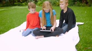 Slowmo pushin of three young children playing on a tablet outside in a park. The youngest looks up and thinks about what the other two are doing.