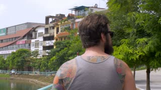 Steadicam of a bearded young hipster man wearing a grey tank top t shirt with colorful tattoos (with release) who is waiving to people on the street as he walks along a lake outside on a warm summer day in a foreign land.