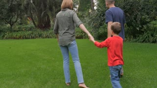 Steadicam of a father and mother holding hands with their son shot from behind as they walk through a park barefoot