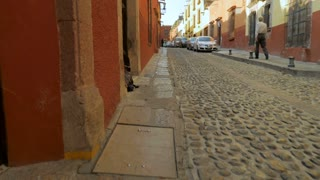 Steadicam shot of the cobblestone streets of San Miguel de Allende Mexico in slow motion as the camera walks by a beggar sitting in the street.