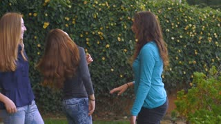 Teenage girls laughing and playing outside in slow motion