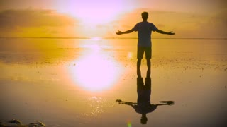 Thankful man stands in still water of the ocean with hands reaching out towards the sun in a worship pose then moving into a lotus position looking for inspiration at sunrise or sunset with his reflection in the water below him.
