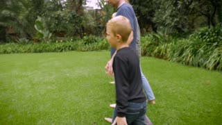 The camera follows a family of five holding hands walking together barefoot in the grass - slowmo steadicam