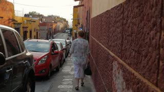 The camera follows tourists in the streets of San Miguel de Allende steadicam slow motion shot.