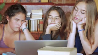 Three attractive bored students look at the same computer laptop together and try to stay focused on a school assignment or project