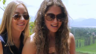 Three attractive teen girls laugh and talk with each other outside in slowmo in the summer on a deck overlooking a beautiful view
