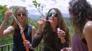 Three beautiful teen girls wearing sunglasses blowing bubbles on a carefree summer day in slow motion