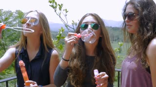 Three beautiful teenage girls outside on a deck in the summer having fun with bubbles in slow mo