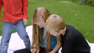 Three cute sibling children sit on a blanket outside and play on a tablet in slowmo with steadicam. The younger brothers and older sister are focusing intently on their technology together.