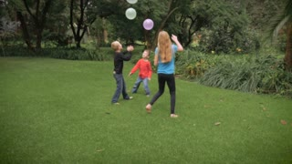 Three cute, young kids play together in a park with balloons in slowmo