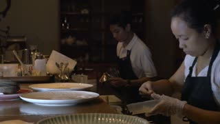 Three dessert chefs prepare gourmet dishes at a restaurant in an assembly fashion