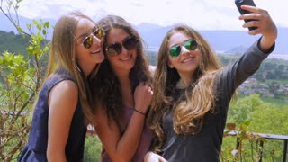 Three gorgeous teenage girls take multiple selfies and look at their cell phone in slow mo while standing outside on a sunny day with mountains and green landscape in the background.