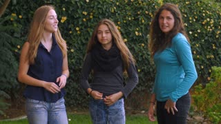 Three lovely teenage girls dance and have fun together in slow motion