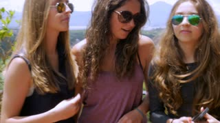 Three lovely teenage girls with beautiful long hair look at their smart phone together, smile, and laugh, in slowmo while standing on a terrace overlooking mountains and a green landscape.