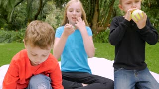 Three prepubescent children try to blow up balloons outside on a blanket in a park - slowmo handheld
