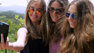 Three teen girls with beautiful long hair take selfies in slowmo during summer break or vacation