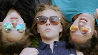 Three teenage girls lying in the grass making silly faces to the camera while wearing sunglasses