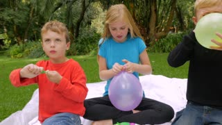 Three young beautiful innocent kids blow up and tie off balloons outside - slowmo handheld