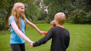Three young children playing ring around the rosie - slowmo. The youngest child does not fall down at the end and laughs.