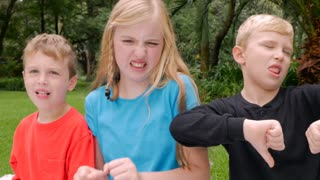 Three young children say yuck and hold their noses in disgust as if something smells or tastes bad outside in a park