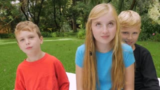 Three young children sitting outside look at the camera and give the thumbs down and crack up in slowmo