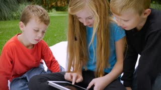 Three young cute, adorable children are completely engaged on their shared tablet - slowmo