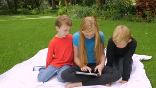 Three young, cute children play on a tablet outside while one swats a mosquito and then they smile and look towards the camera - slow motion push-in