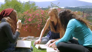Three young girls with long hair studying with books outside in the grass together in slowmo