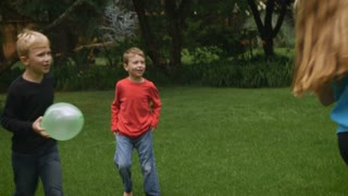 Three young kids including two boys and a girl set up a game outside in a park with balloons - slowmo handheld