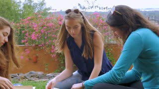 Three young woman read books outside together while sitting on the green grass in slow motion