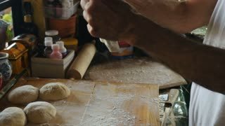 Tilt up and down of a man preparing bread or dough with a rolling pin for pizza on a wooden cutting board in his home kitchen