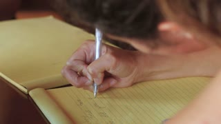 Tilt up close up of beautiful young teenage girls writing with pens and pencils and doing homework together