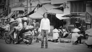 Time lapse of a solitary man wearing a breathing mask to filter out pollution and toxic air stands still as the world around him flies by at a busy market where people are over consuming in black and white.