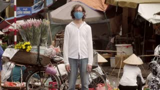 Time lapse of a solitary man wearing a mask to filter out pollution and toxic air stands still as the world around him flies by at a busy market where people are over consuming in color, medium shot.