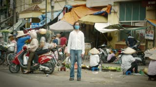 Time lapse of a solitary man wearing a mask to filter out pollution and toxic air stands still as the world around him flies by at a busy market where people are over consuming in color.