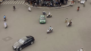 Time-lapse of busy traffic intersection in Hanoi, Vietnam where even though crowed and congested, cars, scooters, and pedestrian people work together without any traffic lights, or rules.