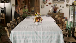 Time lapse of two middle aged women set a large table with dishes, glasses, and place settings for a party